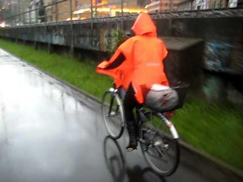 Rainweargirl - rainwear girl in orange colorful gear on the bike.