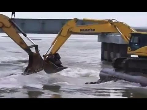 RUSSIANS - Citizens of Russia's Komi Republic board a makeshift ferry due to high water and bad road conditions. They organized a backhoe passage: Two excavators standi...