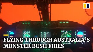 Pilot cockpit view shrouded in orange glow from Australia's bush fires