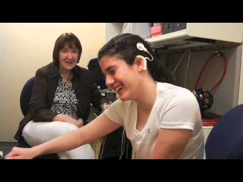 A young woman has her cochlear implant activated for the first time, and is overwhelmed with emotion