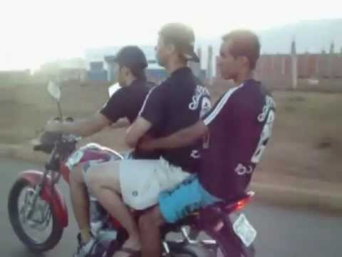 Three guys trying to wheelie motor bike