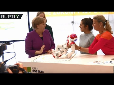 Merkel gets goofy while toying with robot at German Chancellery