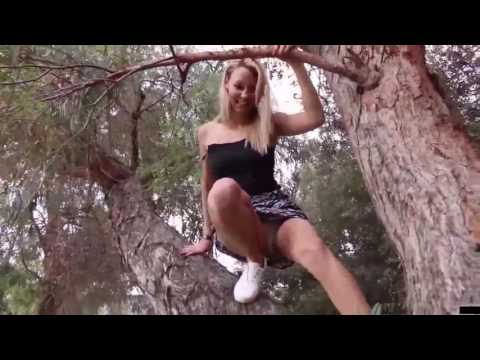 Young blonde Girl climb a tree in a short skirt