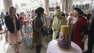 The Queen cuts a 90th birthday cake which was made by Nadiya Hussain, winner of the Great British Bake Off. .