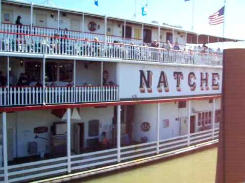 Steamboat - Engine room showing paddle wheel drive system, steam whistles blowing, and the docking procedure of the Natchez steam boat on the Mississippi River at the To...
