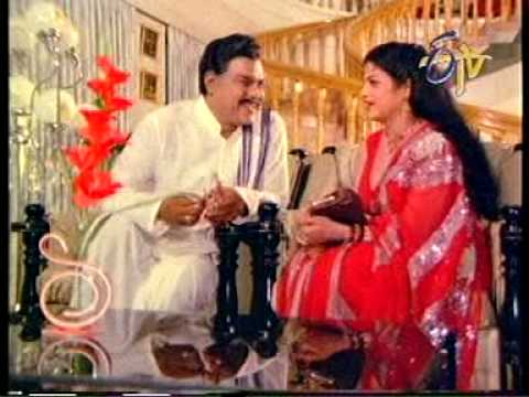 pallu drop - Jayamalini cheekily gives glimpses of her sexy deep cleavage in a sleeveless red blouse to a perverted old politician. The scene is from the movie Muddu Bidda.