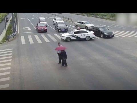 Kiinalainen poliisi pysäyttää liikenteen auttaakseen vanhan miehen risteyksen yli