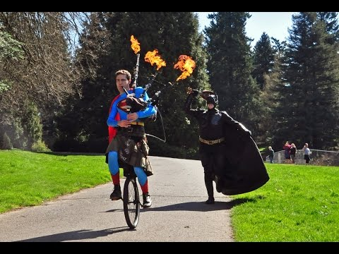 Bagpipe Superman on Unicycle Drowns Out Ukulele Batman by Playing the Superman Theme