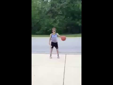Kid wipes out girl on bike with a basketball