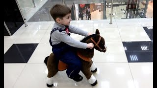 Вадик катается на лошадке в торговом центре.
