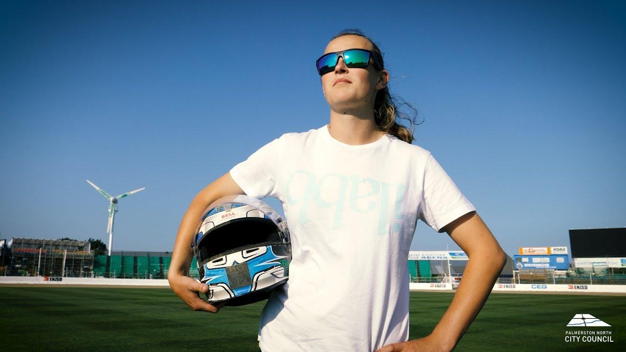 YouTube placeholder image shows Rebecca at the stadium holding her crash helmet.