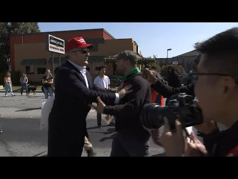 Donald Trump supporters walks through angry crowed