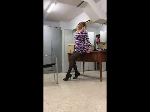 Blond crossdresser secretary wearing a short dress and High Heels