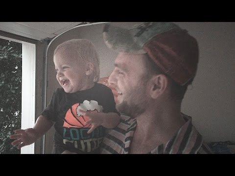 Мъничко детенце се радва на първия летен дъжд в ръцете на татко си