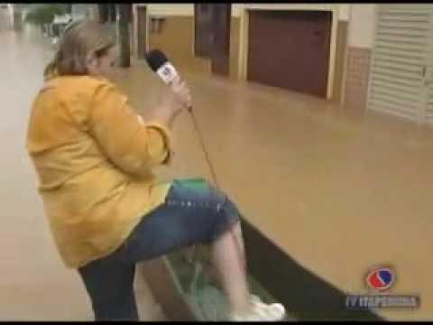 Ivonete de Oliveira da TV Itaperuna-RJ caindo do bote na água das enchentes de 2009