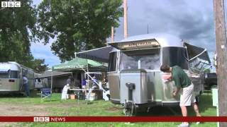 Hundreds of caravan owners have gathered in the US state of South Dakota for an annual rally.The iconic aluminium Airstream motor homes, some of which are more than 80 years old, were reportedly invented by a man whose wife refused to go camping without a kitchen.Source: BBC