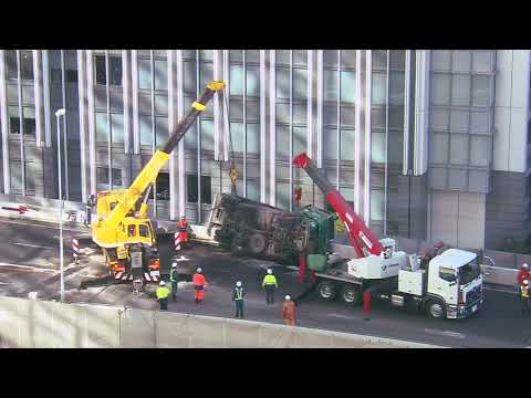 A dump truck dangles over the edge of a highway in downtown Tokyo, following a crash that killed the driver.
