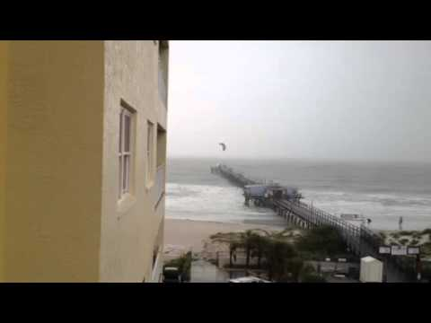 Kite surfer jumps over a pier