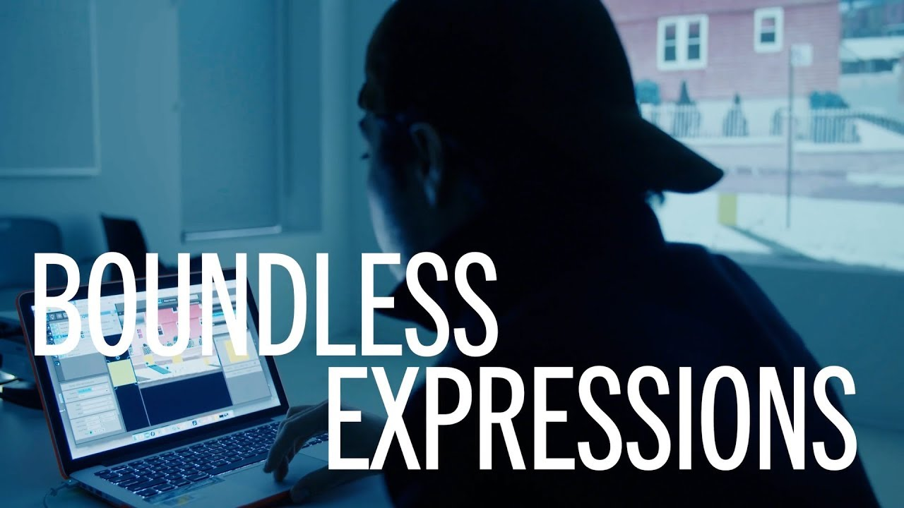 The phrase boundless expressions overlapping an image of a young man in a dark room looking at a screen with his hat on backwards