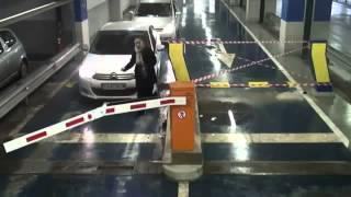 Kobieta chce wjechać na parking, ale na drodze jest szlaban…