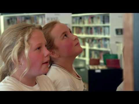 YouTube placeholder image shows two young girls in a library.