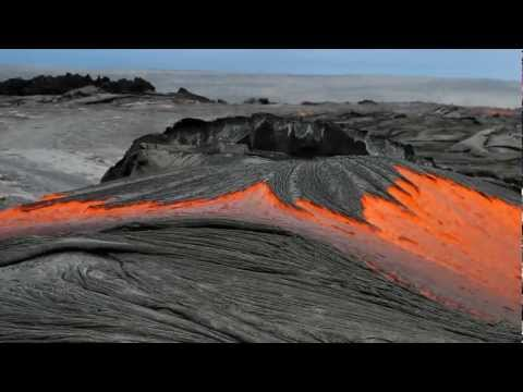 lava - A surge of lava spews out of a rupture in the lava tube system and is heading down steep cliffs, or pali in Hawaiian. This strong flow is being supplied lava...