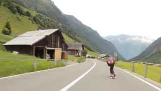 a raw run down a pass in the swiss alps on their national day, a lot of cars.