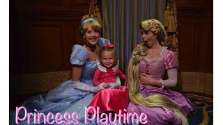 Lane plays with Cinderella and Rapunzel in Princess Fairytale Hall in the Walt Disney World's Magic Kingdom.