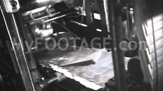 MS of collated 1930's newspapers coming off of a printing press en masse, ready to distribute to the public. This clip available for immediate purchase, clean, ...
