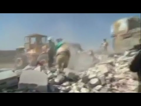 The images show men running through rubble and smoke rising from the ground. A loud explosion is heard on the recording.
