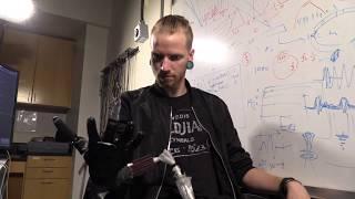Человек с бионической рукой учится играть на пианино