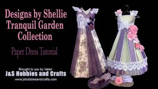 "Take a stroll in Tranquil Gardens with us. This beautiful, 3D dress was made with our very own Designs by Shellie Tranquil Garden paper collection. Adorned with Prima Flowers, Venise Lace, and flat back pearls. There's even a FREE pattern to make this dress located at https://jshobbiesandcrafts.com/?page_id=506 Blog. You too can make this cute little 12"" tall dress when you buy your materials at www.jshobbiesandcrafts.com today!Products used:• Designs by Shellie Tranquil Garden Paper Collection• Prima Marketing Flowers - Haley• Tim Holtz Display Hangers• Tyvek Envelopes 10x13 (Pkg of 5)• Flat Back Pearl Trim White and Ivory• Beaded Sequin Lace 3""• Kaisercraft Mini Blooms Burgandy• Scalloped Venise Lace White 1 ¾""• Bling on a Roll Silver• Scor-Tape• Art Glitter Glue• Metal Glue Tip"