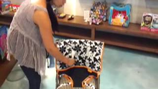This is a compact fabric travel high chair by My Little Seat that folds down to the size of a diaper in its own matching bag. Available...