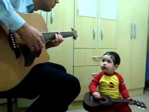 Hermoso bebé tocando guitarra.