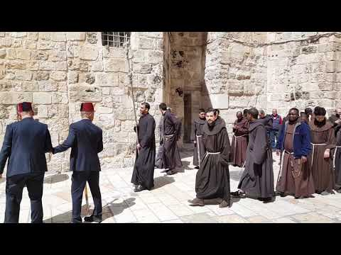 Why are there four Mslims at the head of the franciscans procession in Jerusalem