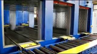 These LEWCO curing ovens (models NS-CVC03EVD) were designed with (3) independently controlled lanes of dual strand chain conveyors.  The control system will automatically select which lane is ready to receive parts, then it will index those parts through the ovens to yield consistent dwell times at a constant temperature. At the entrance and exits outside the ovens, a custom designed material handling system consists of chain driven roller conveyors, pneumatic pop-ups, pop-up chain transfers, and a motorized swing gate conveyor.