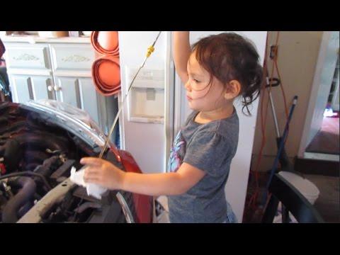 Leniwy tata z córką wymienia olej w samochodzie