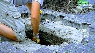 TIPP: WERKZEUG FÜR DIE BAUSTELLE HIER http://amzn.to/2piGq4kHeute wird ein Loch in der gepflasterten Auffahrt repariert. Die Absackung ist direkt über dem Betonrohr, das unter der Auffahrt langläuft. Im Rohr befindet sich viel Sand und Dreck, was wohl mit dem Regenwasser eingespült wurde. Ich vermute mal, dass der Sand aus der Pflasterbettung in das Rohr gewaschen wurde. Das würde allerdings bedeuten, dass das Rohr irgendwo defekt.. also nicht ganz dicht sein müsste. Ich hoffe mal das Rohr ist nicht zerbrochen aber das werden wir erst wissen, wenn wird das Rohr freigelegt haben. Also nehme ich als erstes die Betonpflastersteine an der abgesackten Stelle heraus. Dafür kann man einen Schraubenzieher zur Hilfe nehmen um den ersten Stein herauszubekommen. Danach können weitere Steine einfach mithilfe einer Forke oder Schaufel gelöst und herausgenommen werden. Ich nehme ein paar mehr Steine heraus als abgesackt waren, damit ich genug Platz zum Aufgraben habe. Jetzt kann ich den alten Fugensand leicht entfernen. Hier wurde offensichtlich mit einem Pflasterflies gearbeitet, das kann manchmal für eine Höhere Stabilität des Pflasterung sorgen und gegen Ameisen und Unkraut hilfreich sein. Ich schneide den Bereich mit einem Teppichmesser heraus. :-) das Flies hat hier in der Mitte sogar die Steine gehalten, weil der Sand darunter fehlt. So jetzt werde ich die Stelle bis zum Rohr aufgraben und sehen wo das Problem liegt. Ich lockere den teilweise harten und steinigen Boden mit einem Spaten auf und nehme ihn dann mit einer Plattschaufel heraus. Ich hab jetzt 35cm tief gegraben und das Betonrohr schon gefunden. Scheinbar sind zwei Teile der Beton-Leitung nicht ganz zusammen. Durch den 3 cm Spalt wurde der Sand langsam mit jedem Regenguss ins Rohr gespült. Ich repariere die Leitung in diesem Fall unkonventionell. Dafür wickle ich zunächst ein Stück Stoff und die Stelle am Rohr und fixiere es mit Draht. Nun werde ich die Verbindung mit einem Ring aus Beton stabilisieren. Durch den 