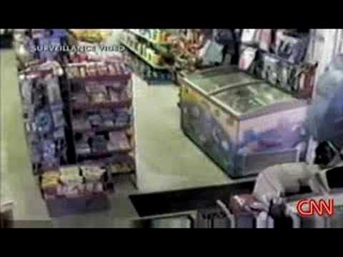 video que muestra a un hombre atracando una tienda con una palmera