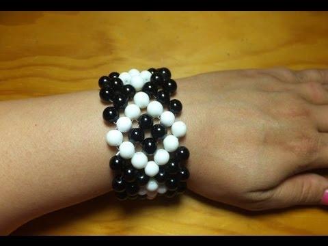 Pulsera brazalete con bolas blancas y negras.