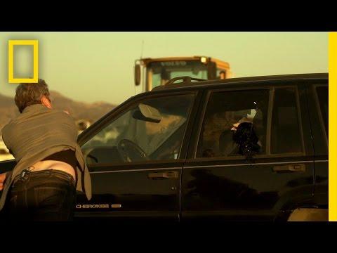這名男子拿著搥子猛敲都無法打爆車窗後,身旁的朋友笑著給他一塊小碎片叫他往車窗丟…