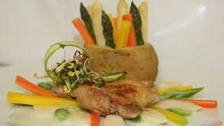 Knuspriges Hähnchensteak mit Spargelragout und bunten Möhren gefüllter Kartoffel