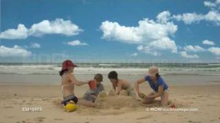Time-lapse of four children building sand castle on beach, Byron Bay, New South Wales, Australia