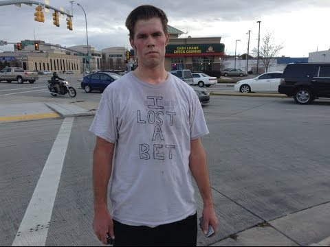 Brother loses bet and has to dance on busy intersection. People walking by join him.