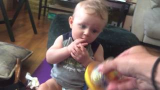 Baby Isaac is surprised by his auntie shaking his toy.