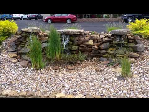 Natural stone waterfall with dwarf cattails at Misty Meadows Retirement Community.