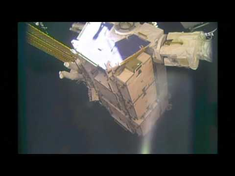 Two astronauts step outside the International Space Station to upgrade batteries.