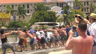 Turistas e locais se seguram em cerca de aeroporto vizinho a praia caribenha para sentir rajada de vento como a que matou uma turista neozelandesa.