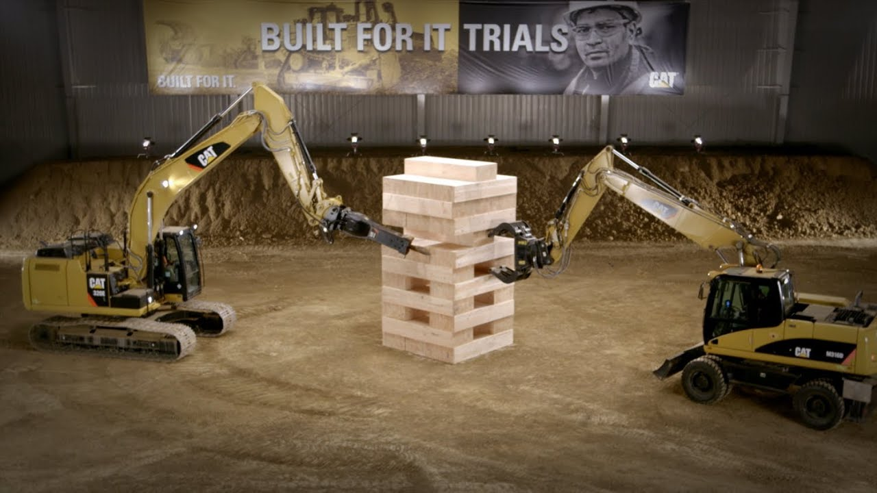 Watch five Cat machines, including excavators, against a mountain of massive JENGA? blocks!