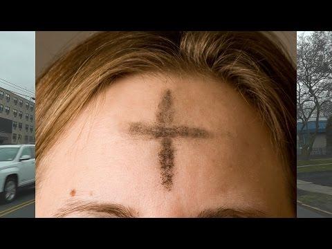 Рисует крест на лбу